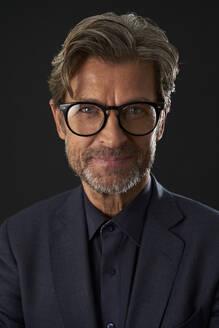 Portrait of smiling mature businessman wearing glasses against dark background - PHDF00008