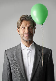 Portrait of smiling businessman with green balloon - PHDF00017