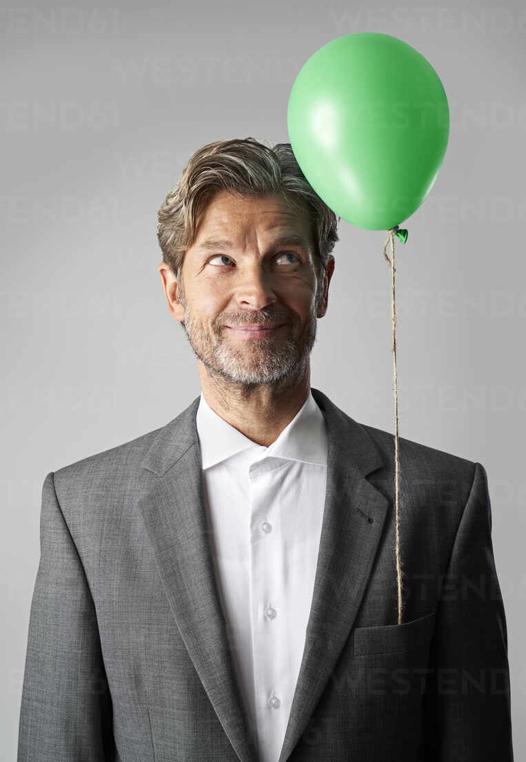 Portrait of smiling businessman with green balloon - PHDF00017 - Isabella Bellnini/Westend61