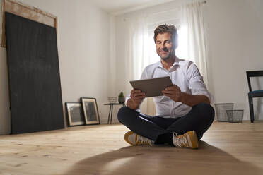 Portrait of smiling mature man sitting on the floor at home using digital tablet - PHDF00020