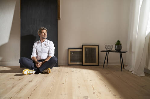 Portrait of relaxed mature man sitting on the floor at home looking at distance - PHDF00023