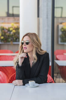 Businesswoman with sunglasses after work with a coffee, looking sideways - DLTSF00301