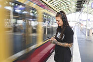 Tattooed young woman with headphones standing at platform using smartphone, Berlin, Germany - WPEF02373
