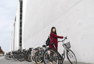 Businesswoman taking bicycle in the background of modern building - AHSF01527