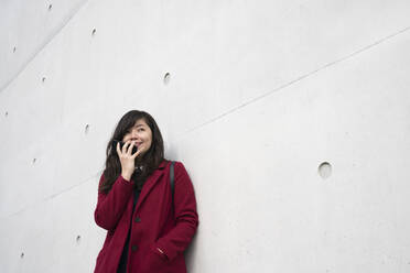 Portrait of modern businesswoman using smartphone in front of a wall - AHSF01533