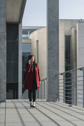 Businesswoman walking on a bridge near to modern building and using smartphone - AHSF01554