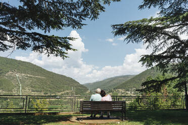 Back view of senior couple sitting on a bench looking at view, Jaca, Spain - AHSF01560