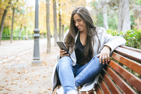 Smiling woman sitting on a park bench using smartphone - KIJF02826