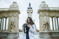 Smiling woman with a camera standing in front of Alfonso XII monument in El Retiro park, Madrid, Spain - KIJF02832