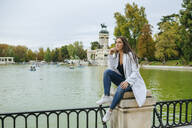 Pensive woman sitting near a lake in El Retiro park, Madrid, Spain - KIJF02838