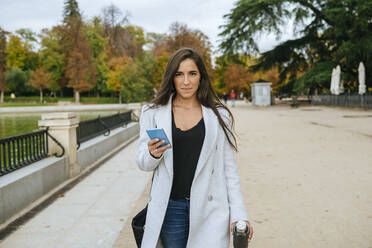 Woman walking through a park holding her smartphone - KIJF02841