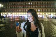 Woman using her smartphone on Plaza Mayor at night, Madrid, Spain - KIJF02847