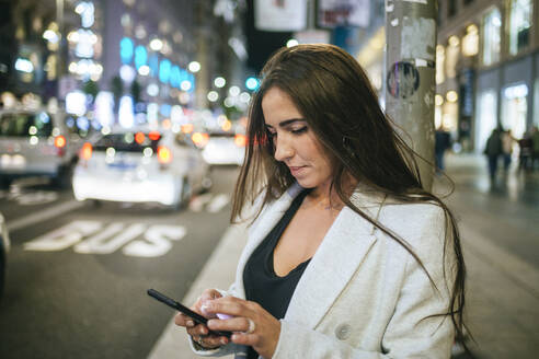 Woman using her smartphone in the street at night - KIJF02853
