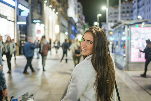 Portrait of a smiling woman walking down shopping street at night - KIJF02856