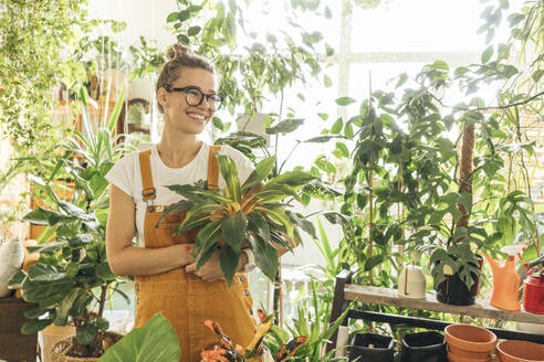 Happy young woman holding a plant in a small gardening shop - VPIF01840