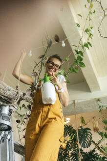 Happy young woman standing on a ladder caring for plants in a small shop - VPIF01843