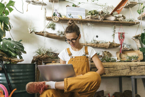 Young woman using laptop in a small gardening shop - VPIF01849