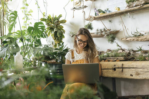 Happy young woman using laptop in a small gardening shop - VPIF01852