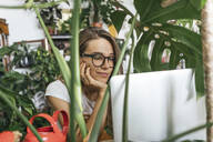 Young woman using laptop surrounded by plants - VPIF01855