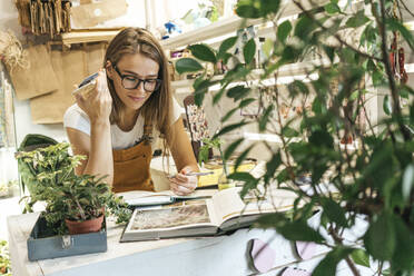 Young woman with smartphone taking notes in a small gardening shop - VPIF01864