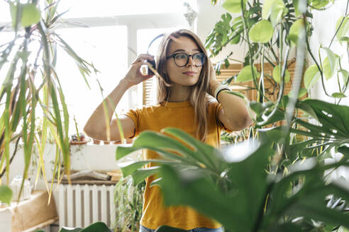 Young woman surrounded by plants listening to music with headphones - VPIF01876