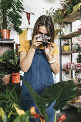 Young woman taking pictures of plants in a small gardening shop - VPIF01888