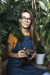 Portrait of a young woman with a camera in a small gardening shop - VPIF01891