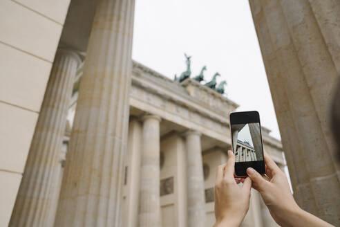 Crop view of hands taking photo of Branderburg gate with smartphone, Berlin, Germany - AHSF01569
