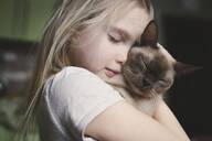 Little girl cuddling with her Burma cat - EYAF00714