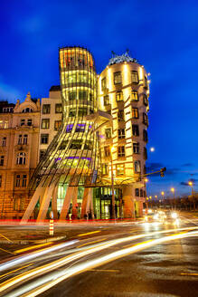 Czech Republic, Prague, Vehicle light trails in front of Dancing House at dusk - YRF00224