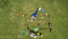 View from above of a gardener in laying on the grass with all the tools he need for take care of garden - VEGF00987