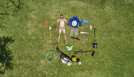 View from above of a gardener in laying on the grass with all the tools he need for take care of garden - VEGF00990