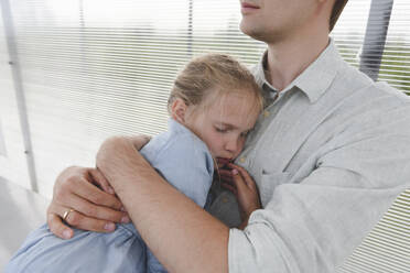 Father hugging his sleeping daughter at a bus station - EYAF00733
