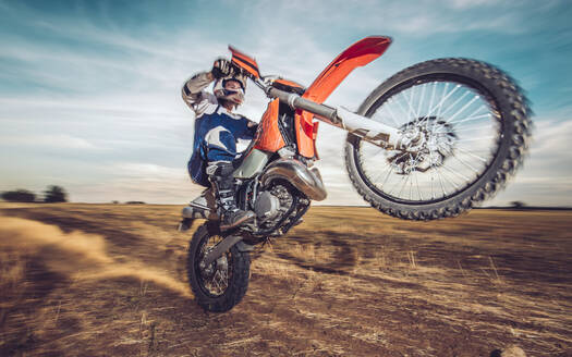 Motocross driver performing wheelie - MTBF00239