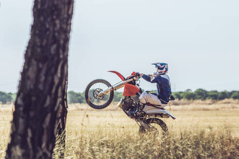 Motocross driver performing wheelie - MTBF00242