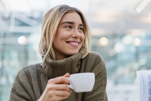 Portrait of a smiling young woman holding cup of coffee looking away - DIGF08973