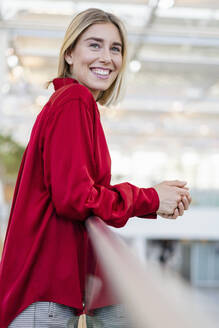 Portrait of a smiling young businesswoman standing at a railing - DIGF08991