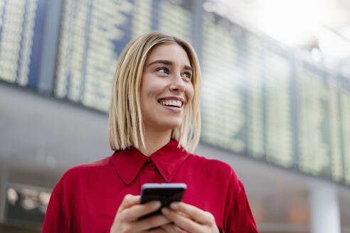 Smiling young businesswoman with cell phone at arrival departure board at the airport - DIGF08997