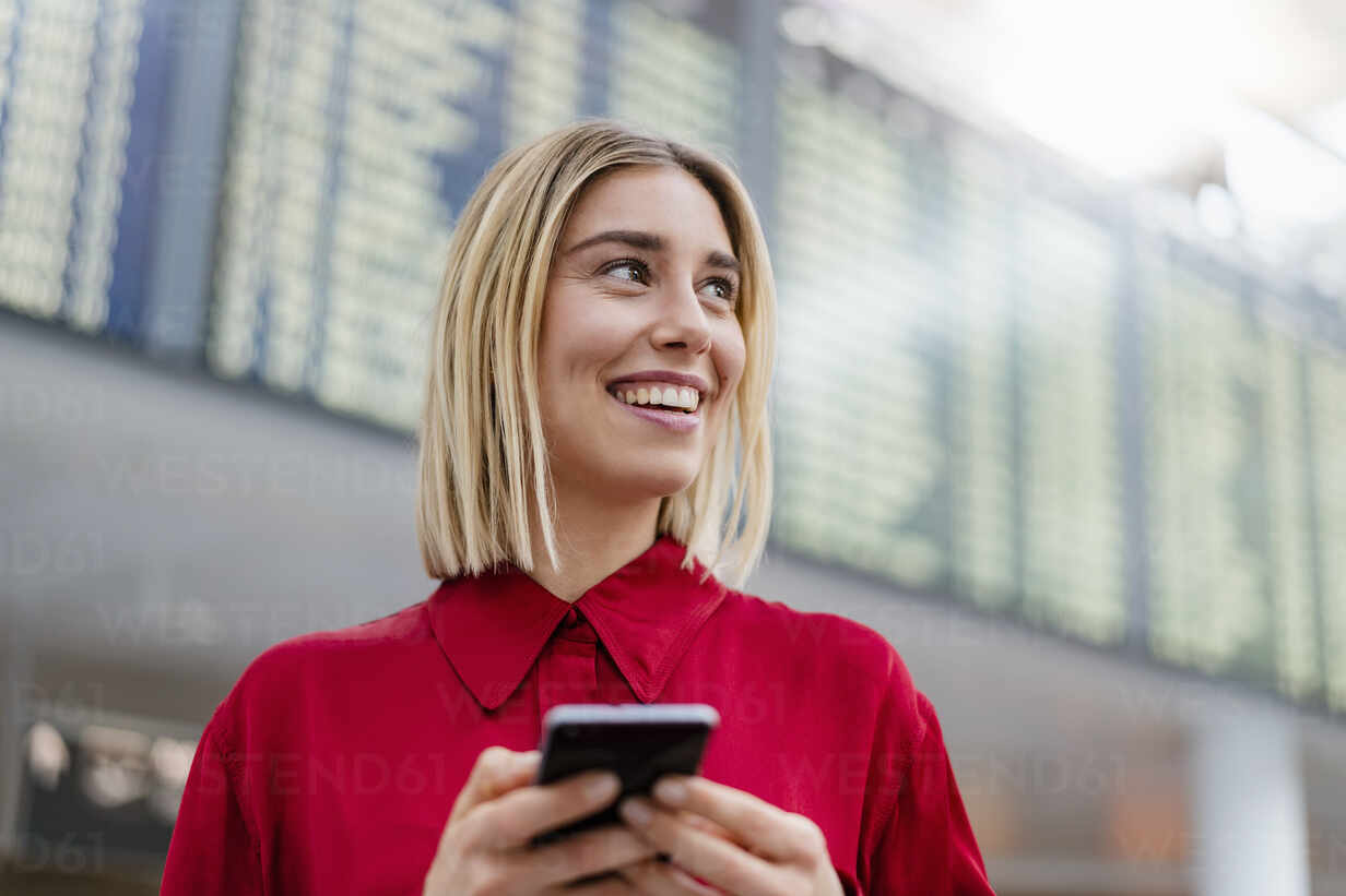 Smiling young businesswoman with cell phone at arrival departure board at the airport - DIGF08997 - Daniel Ingold/Westend61