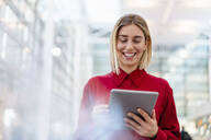 Happy young businesswoman wearing red shirt using tablet - DIGF09006