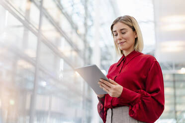 Young businesswoman wearing red shirt using tablet - DIGF09009