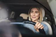 Portrait of smiling young woman driving a car - DIGF09018