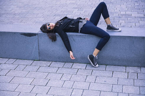 Woman with sunglasses lying on concrete bench - DHEF00007