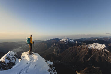 Mountaineer standing on top of a snowy mountain enjoying the view, Lecco, Italy - MCVF00096