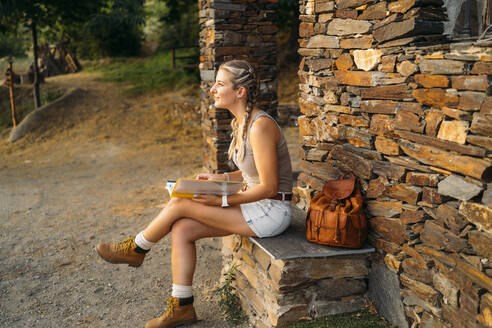 Woman with folder sitting at a stone house in the countryside - MPPF00348