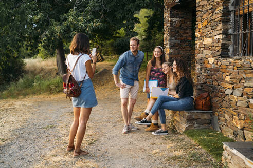 Woman taking smartphone picture of friends at a stone house in the countryside - MPPF00351