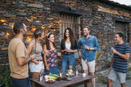Group of friends talking and drinking outdoors at a stone house - MPPF00360