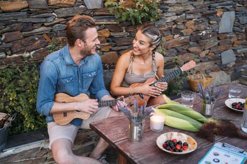 Happy couple playing ukulele outdoors at a stone house - MPPF00363