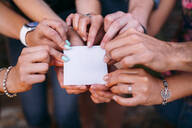 Close-up of friends holding a blank card - MPPF00369
