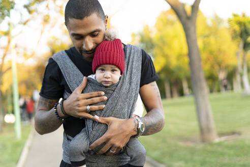 Young father carrying baby son in a baby sling - ERRF02211